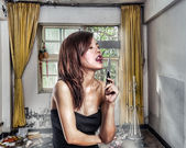Chinese woman in abandoned aprtment about to lick a knife — Stock Photo