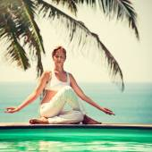 Woman practicing yoga at seashore — Stock Photo