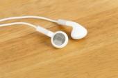 White earphone on wooden table — Stock Photo