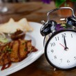 Clock on Wooden Table with steak on background, Lunch Time Conce — Stock Photo #55861823