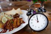 Clock on Wooden Table with steak on background, Lunch Time Conce — Stock Photo