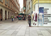 Beggar standing next to a fashion store — Stock Photo