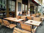 Mature couple sitting in an empty street cafe — Stock Photo