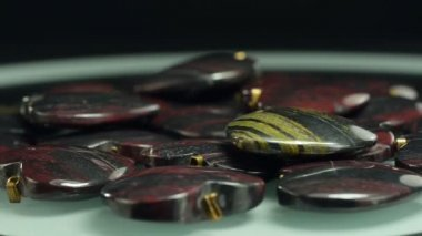 Rotating iron tiger-eye carved stone hearts — Stock Video