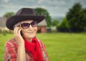 Old cowgirl calling by cell phone and walking at ranch — Stock Photo
