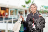 Grey haired woman shopping in mall — Stock Photo