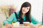 Asian woman having cup of coffee and icecream cake in cafe — Stock Photo