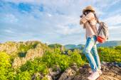 Hiker woman with camera enjoy the view at sunrise mountain peak — Stock Photo