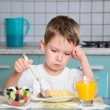 Sad little boy sits at the dining table and looking in the plate — Stock Photo #51811213
