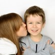 Girl kissing little cheerful boy on light gray background. he fo — Stock Photo #53647755