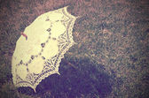 Lacy parasol on the grass. tinted vintage — Stock Photo