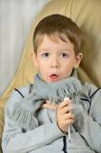 Sick boy coughing and holding a thermometer — Stock Photo