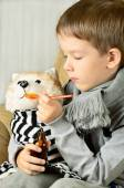 Little boy feeds medicinal syrup the toy dog — Stock Photo