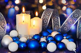 Lighted candles and blue white Christmas tree decorations on the — Stock Photo
