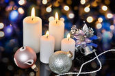 Four white lighted candles and Christmas decorations on a bokeh — Stock Photo