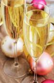 Two glasses with champagne and Christmas tree decorations on the — Stock Photo
