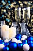 Burning candles, Christmas ornaments and champagne glasses — Stock Photo