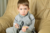 Sad boy holding a thermometer and pills horizontal — Foto de Stock