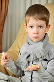 Boy holding a thermometer and pills vertical — Stockfoto