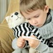 Little boy looking at the thermometer and holding a toy dog — Stock Photo #60615857