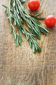 Sprigs of rosemary and cherry tomatoes on a wooden board top vie — Stock Photo