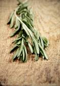Toning effect sprigs of rosemary on a wooden board closeup verti — Stock Photo
