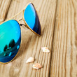 Blue mirrored sunglasses wiht reflection of martini glass on the — Stock Photo #65661585