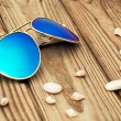 Blue mirrored sunglasses and shells on the wooden background clo — Stock Photo #65661587