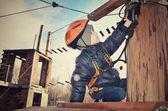 Tinted image little boy sits on suspension bridge and adjusts eq — Stock Photo