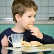 Little boy bites cookies, sitting at the dinner table.  horizont — Stock Photo #72901169