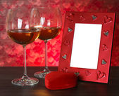 Two glasses of wine, red heart and photo frame. — Stock Photo