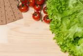 Lettuce, tomatoes and rye bread on wooden background — Stock Photo