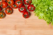 Lettuce and tomatoes on wooden background — Stock Photo