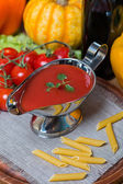 Tomato sauce in a white sauce boat with fresh ingredients — Stock Photo