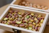 Green pistachio nuts without shell in a wooden box — Stock Photo