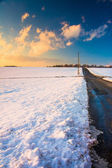 Country road and snow covered fields at sunset, in rural York Co — Foto Stock