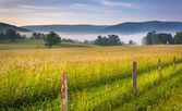 Farm field and distant mountains on a foggy morning in the rural — Stock Photo