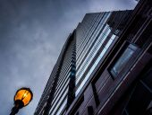 Looking up at a modern building and streetlight under a cloudy s — Stock Photo