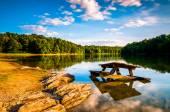 Rocks and a picnic table in Lake Marburg, at Codorus State Park, — Stock Photo