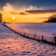Sunset over a fence in a snow covered farm field in rural Carrol — Stock Photo #52605111