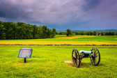 Storm clouds over a cannon and sign in a field at Gettysburg, Pe — Stock Photo