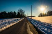 Sun over a country road through snow-covered fields in rural Yor — Stock fotografie