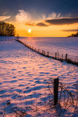 Sunset over a fence in a snow covered farm field in rural Carrol — Stock Photo