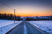 Sunset over a road through a snow-covered field in rural York Co — Stock fotografie
