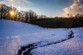 Sunset over a stream in a snow-covered field in rural Baltimore — Stock Photo