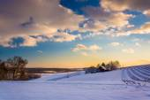 View of snow covered farm fields and rolling hills at sunset in  — Stock Photo