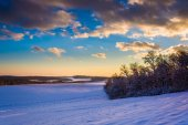 View of snow covered rolling hills and farm fields at sunset in  — Stock Photo