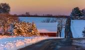 Winter view of a country road and red barn at sunset in rural Yo — Stock Photo