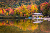Boathouse and fall colors reflecting in Echo Lake, in Franconia  — Stock Photo