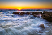 Rocks and waves in the Atlantic Ocean at sunrise in Palm Coast,  — Stock Photo